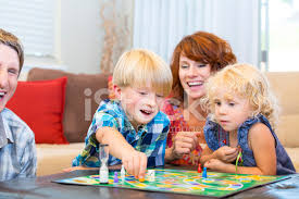 Happy Family With Two Kids Having Fun Playing Board Games