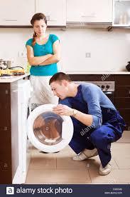 Housewife Watching As Worker Repairing Washing Machine