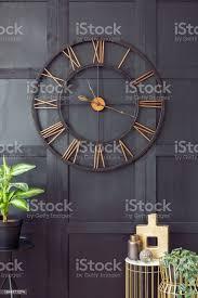 echtes foto mit nahaufnahme der großen uhr hängen schwarze wand im dunklen wohnzimmer interieur mit goldfarbenen accessoires und frischen pflanzen