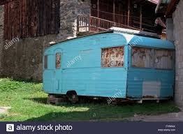 Old Rusty Jacked Up Trailer Home Standing On A Field Between Houses Made Of Boulders
