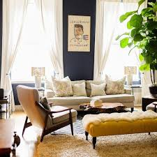 The mustard yellow ottoman keeps with the room s neutral hues yet