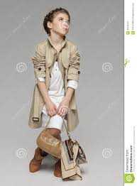 fashion little wearing beige trench coat holding handbag