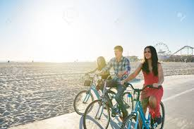 Three Friends Riding Bikes Together On Santa Monica Beach With