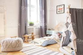 graue vorhänge am fenster und hocker auf teppich in jungen schlafzimmer innenraum mit poster über blauen bett echtes foto stockfoto und mehr bilder