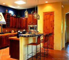 A Bold Spicy Mexican Kitchen With Golden Adobe Walls Rich Wood Cabinets Blue Accents Combination Of Tile And Concrete Countertops