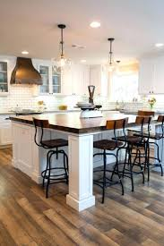 rustic beams and pendant lights over a large kitchen island light