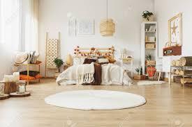 geräumiges schlafzimmer im skandinavischen stil mit einem kingsize bett einem runden teppich in der mitte eines zimmers und vielen baumstämmen