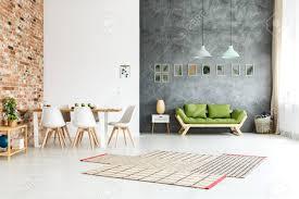 ffnen sie boden haus mit mauer im esszimmer und grünen grünen sofa gegen dunkle texturierte wand in hellen wohnzimmer