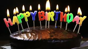 lighted candles on a happy birthday cake candles with the words happy birthday on a