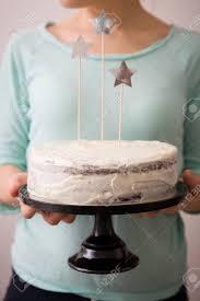 hände der frau köstliche hausgemachte geburtstag weißer kuchen halten verziert mit sternen hellblauen hintergrund backen zu hause für