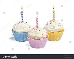 Three cupcakes with candle on white background
