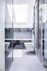 schwarz weiß badezimmer interieur mit reflektierenden fliesen wckeramik und ein helles licht das durch ein dachfenster stockfoto und mehr bilder