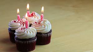 Four chocolate birthday cupcakes with one burning pink candle in each one HD HD