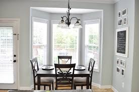 Tiny Open Dining Area With Dark Table And Simple Chairs Under Interesting Chandelier Near White Bay Room Window Treatment Ideas On Grey Painted Wall