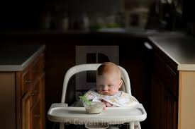 Baby Boy Looking At Food In Bowl While Sitting On High Chair ...