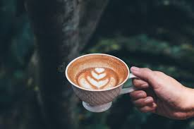 Download A Hand Holding Cup Of Hot Latte Coffee With Heart Art In Green