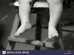 Two Baby Legs Sitting In A High Chair In Black And White ...