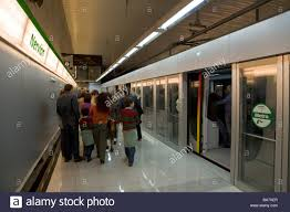 Passengers leaving a metro tube train with barriers and doors open