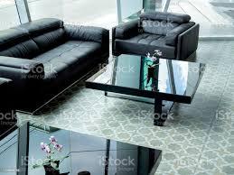 modernes schwarzes ledersofa und schwarzer glastisch auf fliesenboden im wohnzimmer stockfoto und mehr bilder behaglich