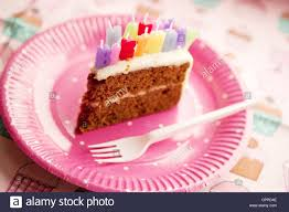 A slice of birthday cake with happy birthday candles set on a pink paper plate on a cupcake patterned background