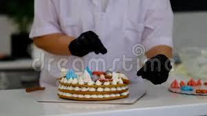 frau dekoriert einen kuchen in der küche patissier bei der