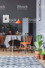 esszimmerinterieur mit tisch stühle schwarz und orange pflanzen und gemusterten teppich stockfoto und mehr bilder alt