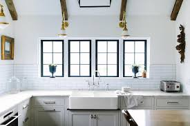 dual farmhouse kitchen sink with glass and brass swing arm sconces