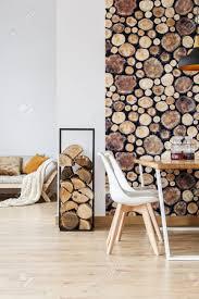 warmes esszimmer inspiriert vom herbstwald mit schlichten möbeln brennholz und tapeten