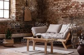 holztisch vor beige sofa im wohnzimmer interieur im wabi sabi stil mit pflanzen und roten backsteinmauer echtes foto stockfoto und mehr bilder