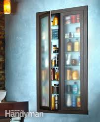 Two Boxes Of Built In Shelves Joined Together And Covered By Glass Doors