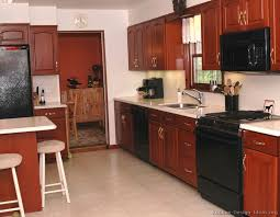 Traditional Medium Wood Cherry Kitchen Cabinets With Black Appliances