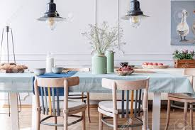 Wooden Chairs At Table With Flowers And Food In White Cottage..