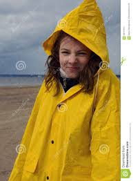 a beautiful in a yellow raincoat is standing in the rain in