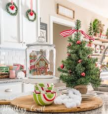 Christmas Kitchen Island Vignette Featuring A Village House In Glass Canister