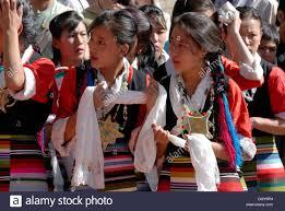 tibetan girls wearing traditional costumes holding good luck