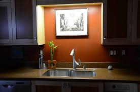 stylish light kitchen sink and gooseneck lighting in kitchen