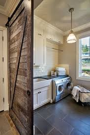 rustic laundry room featuring a sliding barn door gray tile