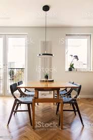 stilvolle und gemütliche esszimmer interieur mit designfamilietisch stühle und le große sonnige fenster weiße und gelbe wände aus marmor und braune