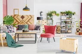 holzkiste nahe rotem stuhl und tisch im geräumigen wohnzimmer interieur mit monstera blatt