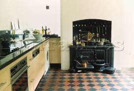 Fitted Kitchen With Vintage Cast Iron Stove And Encaustic Floor Tiles