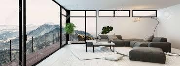 großes modernes glas ummauerten wohnzimmer innenraum mit blick auf berggipfel und täler mit einer grauen sitzgruppe couchtisch und balkon im freien