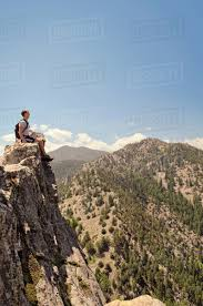Young Man Sitting On Edge Of Mountain Cliff Looking At View