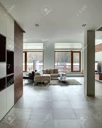 in einem modernen stil mit hellen wänden und hellen fliesen auf dem boden auf der linken seite gibt es eine wand mit dunklen holz nischen mit