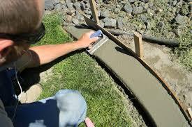 Man Smoothing Concrete Edge In A Garden