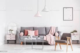 holz sessel und poster in weißen wohnzimmer interieur mit rosa decke auf graue echtes foto stockfoto und mehr bilder decke bettwäsche