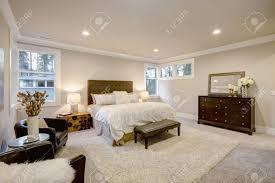 beige und braune master schlafzimmer verfügt über bett mit taupe getuftet kopfteil und bank neben dem bett ein vintage trunk nachttisch neben