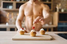 mann mit nacktem körper kocht kuchen mit kirsche auf der