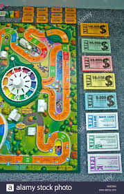 The Game Of Life By Milton Bradley Board All Its Pieces Such As Money Cards Are Spread Out