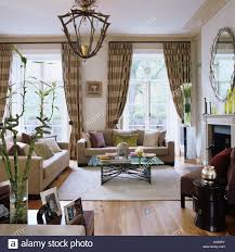 checked curtains in living room with sofas and light fitting stock