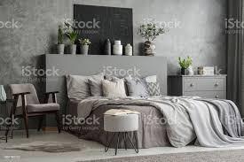 stilvolle schlafzimmer innenraum mit bett mit decken und kissen ein sessel einen hocker eine schublade schrank und eine schwarze gemälde an der wand